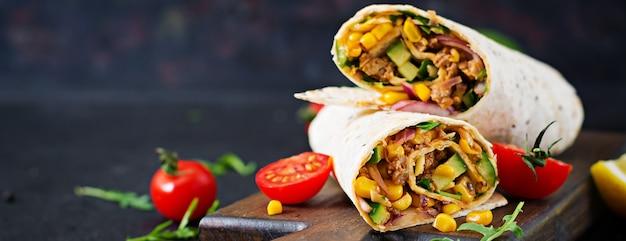 Burrito'somslagen met rundvlees en groenten op zwarte achtergrond. rundvleesburrito, mexicaans eten.