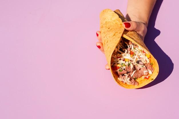 Burrito van de de persoonsholding van de close-up met purpere achtergrond