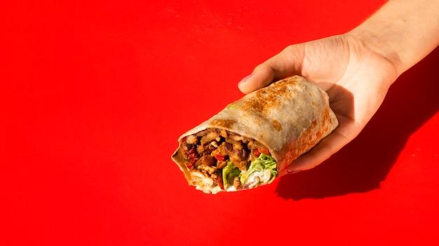 Burrito van de de vrouwenholding van de close-up met exemplaar-ruimte