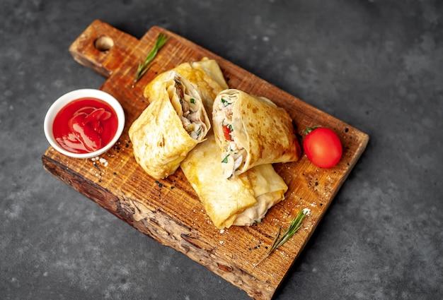 Burrito wraps met kip en groenten, tegen een achtergrond van beton met kopie ruimte voor uw tekst, mexicaanse shoarma