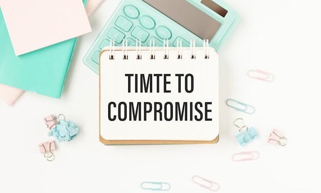 Businesman houdt blocnote met tekst tijd om een compromis te sluiten. witte achtergrond. bedrijf