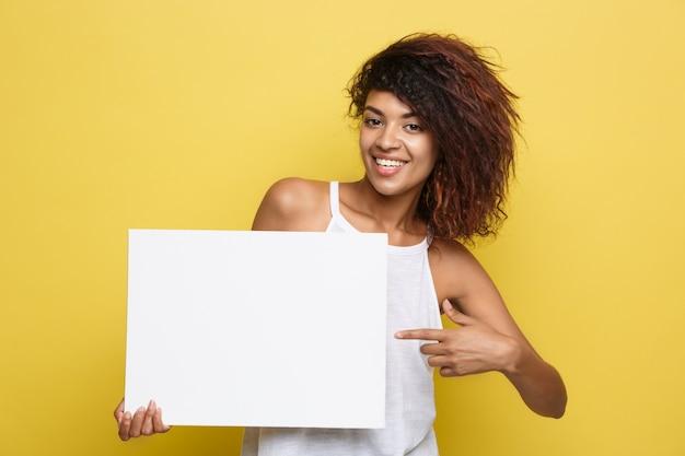 Business concept - close-up portret jonge mooie aantrekkelijke afrikaanse amerikaanse lachende toon duidelijk wit leeg teken. gele pastelstudio achtergrond. kopieer de ruimte.