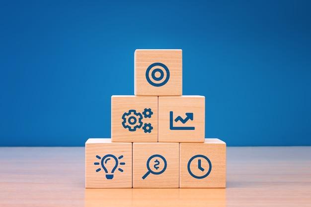 Business concept groeisuccesproces, close-up houtblok met pictogram bedrijfsstrategie en actieplan.