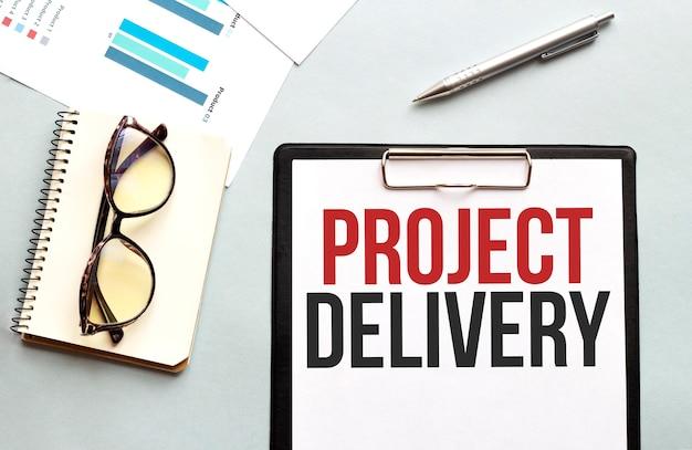 Business concept notebook met tekst project levering vel wit papier voor notities glazen op de witte achtergrond