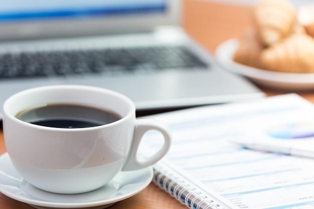 Business desk met koffie, gebak, laptop en zakelijke grafieken