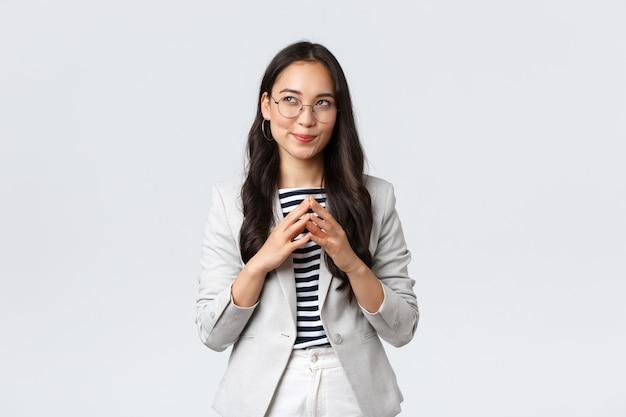 Business, finance en werkgelegenheid, ondernemer en geld concept. creatieve jonge aziatische zakenvrouw heeft een slim idee, denkt na, maakt plannen of bereidt een plan voor, steekt de vinger op en kijkt dromerig op