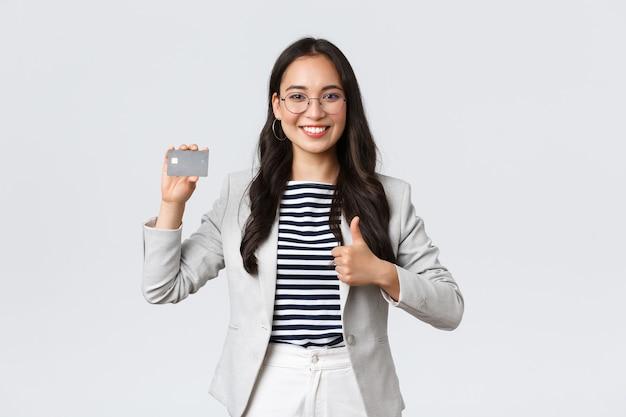 Business, finance en werkgelegenheid, ondernemer en geld concept. professionele vrouwelijke bankbediende, officemanager beveelt creditcard, bankservice aan, duim omhoog