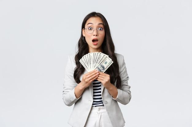 Business, finance en werkgelegenheid, ondernemer en geld concept. verbaasde en sprakeloze jonge aziatische zakenvrouw verdient het eerste salaris voor het verkopen van een huis, houdt contant geld vast en staart verbaasd.