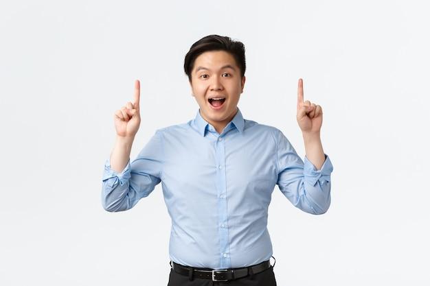 Business, financiën en mensen concept. opgewonden en verbaasde aziatische zakenman in blauw shirt die aankondiging doet, vingers omhoog wijst en camera kijkt, groot nieuws vertelt, witte achtergrond.