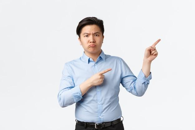 Business, financiën en mensen concept. teleurgesteld sombere aziatische mannelijke kantoormedewerker, verkoper in blauw shirt klaagt over iets ergs, toont de weg, wijzende vingers in de rechterbovenhoek