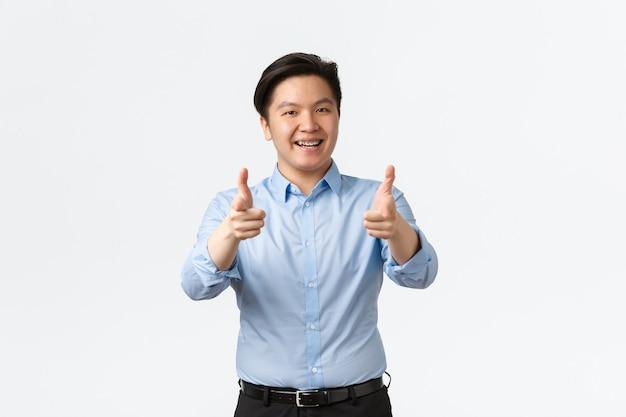 Business, financiën en mensen concept. tevreden aziatische zakenman met tandenbeugels die duimen omhoog laten zien, kantoormedewerker raadt product aan of complimenteert goed werk, witte achtergrond