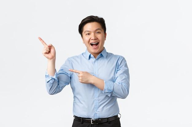 Business, financiën en mensen concept. vrolijke aziatische verkoper in blauw shirt met tandenbeugel, wijzende vingers in de linkerbovenhoek en opgewonden glimlachen, aankondiging tonen, product aanbevelen.