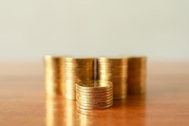 Business, geld, financiën, veiligheid en besparingsconcept. sluit omhoog van stapel gouden muntstukken op houten lijst met exemplaarruimte.
