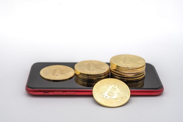 Business, geld, technologie en cryptocurrency-concept. close-up van gouden bitcoin-munten op rode mobiele smartphone met witte achtergrond.