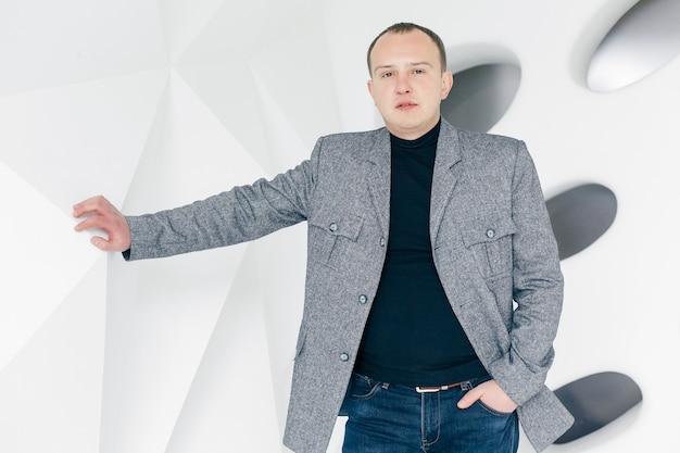 Business, gezondheid, mensen en lifestyle concept - stijlvol. knappe man in jasje. portret van lachende jonge zakenman met gekruiste armen permanent op kantoor en camera kijken.