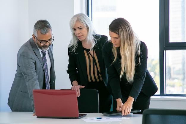 Business group kijken naar projectpresentatie, staande aan de vergadertafel, laptop scherm kijken. gemiddeld schot. zakelijke communicatie concept