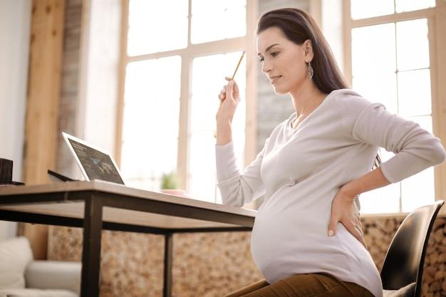 Business idee. lage hoek van meditatieve doordachte zwangere vrouw die met idee op de proppen komt terwijl ze haar rug en stijgend potlood thuis ondersteunt