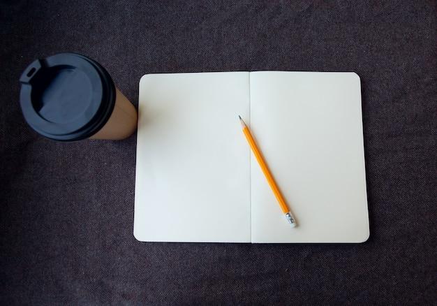 Business, lifestyle, food en coffee concept - potlood, notitieboekje en papieren koffiekopje op een bruine stoffen achtergrond