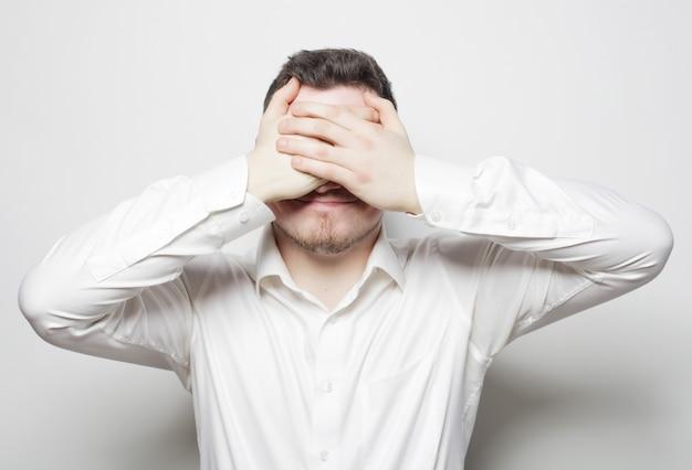Business man dekking ogen met zijn handen
