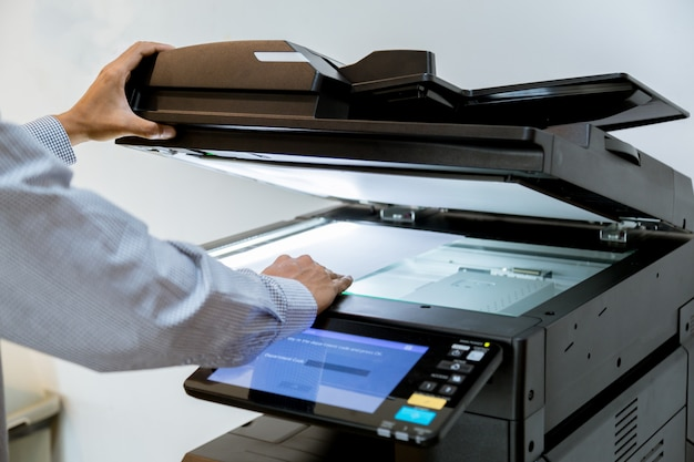 Business man hand drukknop op paneel van printer, printer scanner laser kantoor kopie machine levert start