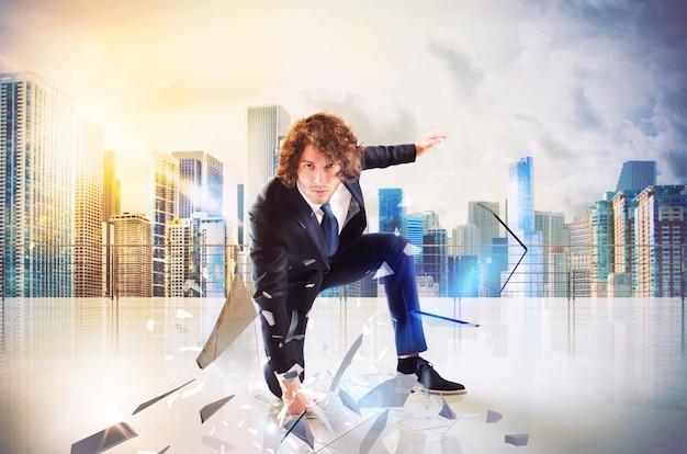 Business man punch met kracht en vastberadenheid in de vloer van het dak