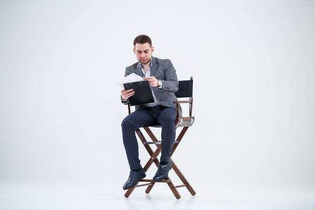Business man zakenman in een pak zittend op een houten stoel en documenten gooit. op een witte achtergrond met gedachten aan een nieuw project