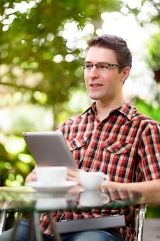 Business man zittend aan tafel in het cafe met behulp van tablet