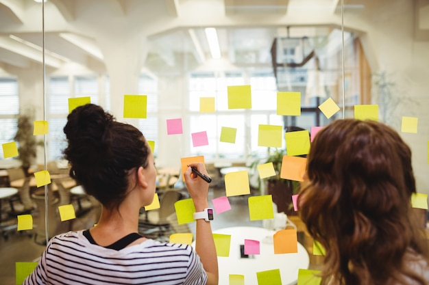 Business managers schrijven op sticky notes