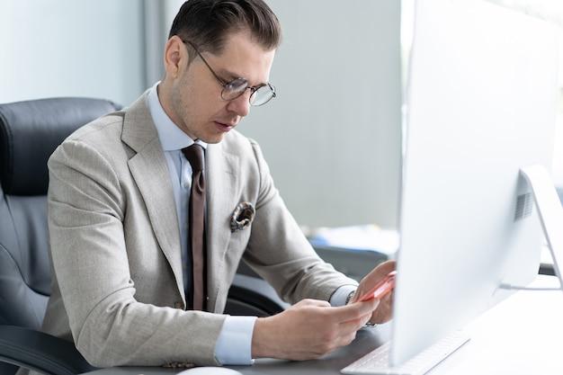 Business, office en technologie concept - zakenman met computer en smartphone op kantoor.