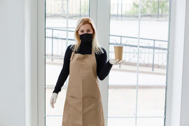 Business owner concept - mooie blanke barista in gezichtsmasker biedt warme koffie in de moderne coffeeshop