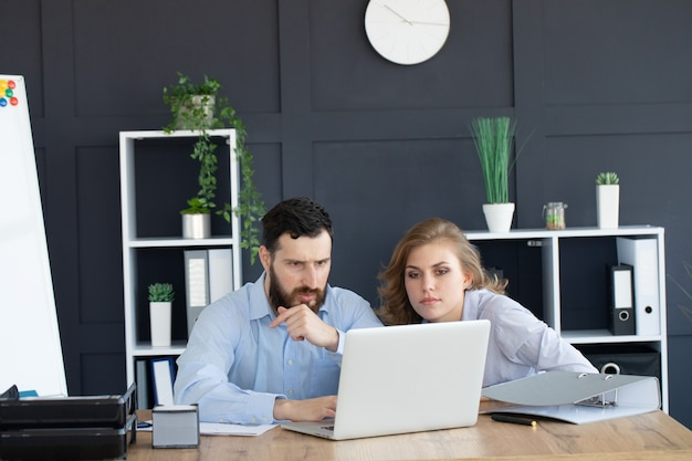 Business paar samen te werken aan project op moderne startup office