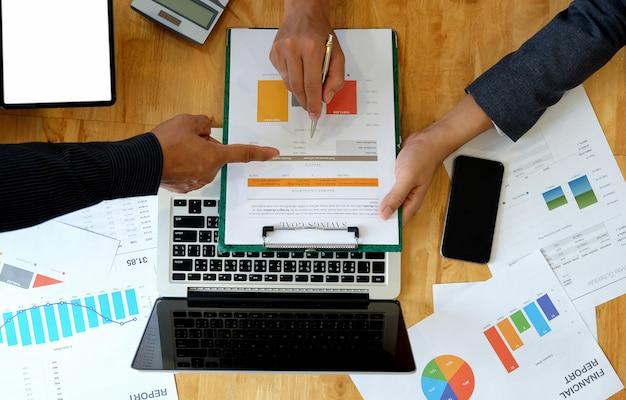 Business team analyseert de gegevens uit de grafiek om klanten op kantoor te presenteren.