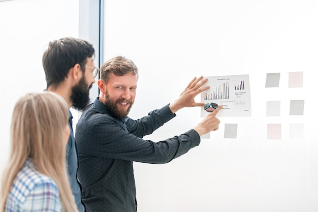 Business team bespreekt financiële schema's staan in het kantoor