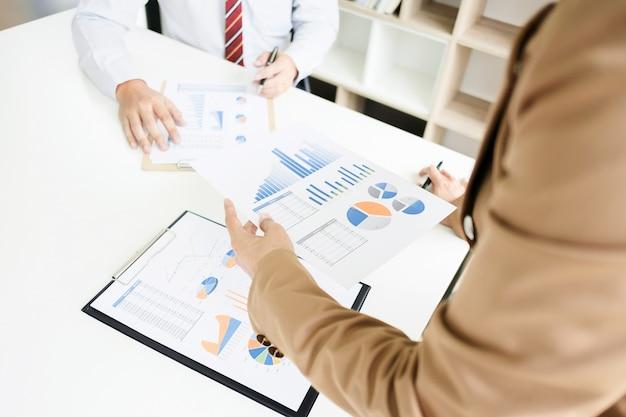 Business team brainstorming bespreken verkoopprestaties op wit bord terwijl presentatie in moderne kantoor kamer