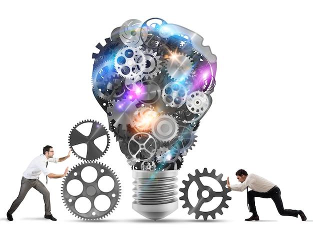 Business team duwt versnellingen naar een geweldige gloeilamp. bouw een ideeconcept