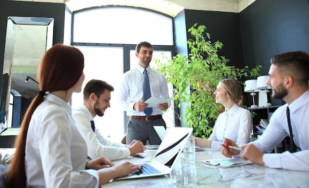 Business team juicht de spreker bij de presentatie van het nieuwe project.