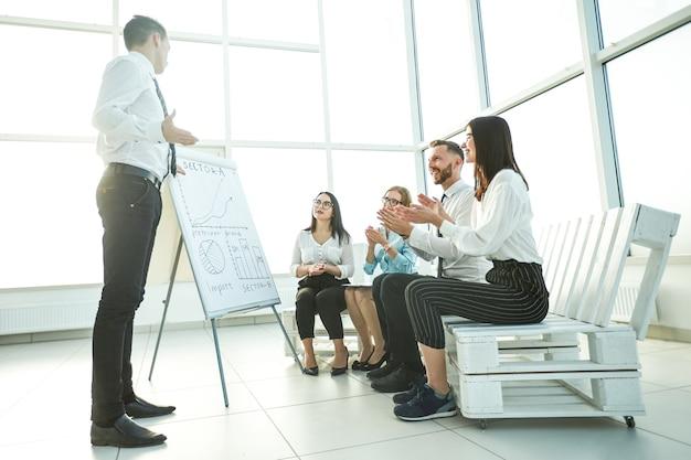 Business team juicht de spreker op een briefing in het nieuwe kantoor. het concept van goed werk