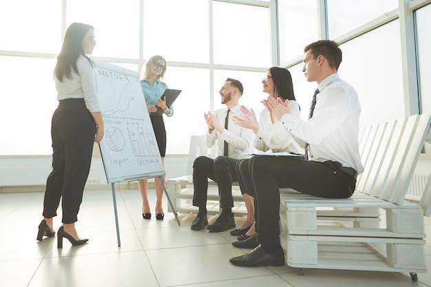 Business team juicht de spreker toe bij de presentatie van het nieuwe project