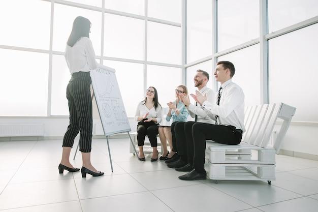 Business team juicht de zakenvrouw toe bij de presentatie van het nieuwe project