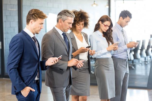 Business team met behulp van hun mobiele telefoon op kantoor