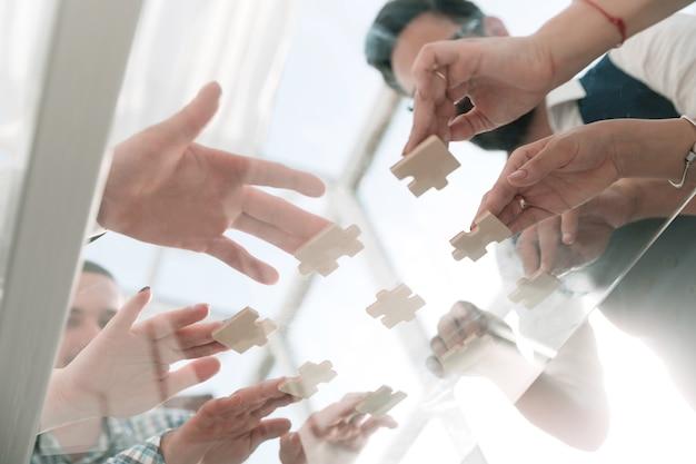 Business team met stukjes puzzel op kantoor, onderaanzicht
