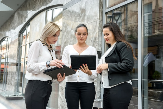 Business team met tablets poseren buiten kantoorgebouw. drie dames die rechtstreeks op tabletscherm kijken