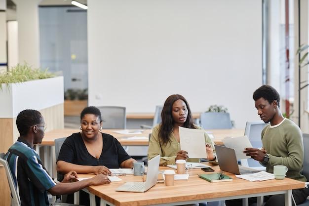 Business team met vergadering aan grote kantoortafel bespreken plannen en rapporten