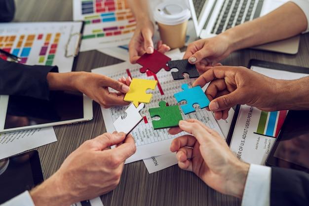 Business team proberen stukjes van een puzzel met elkaar te verbinden