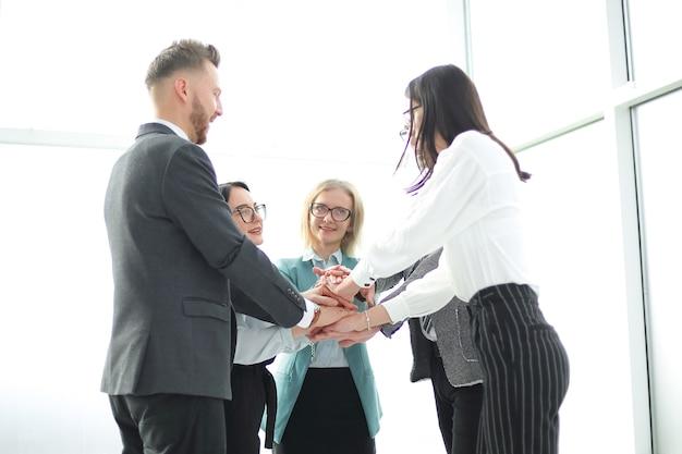 Business team toont hun eenheid terwijl ze op kantoor staan