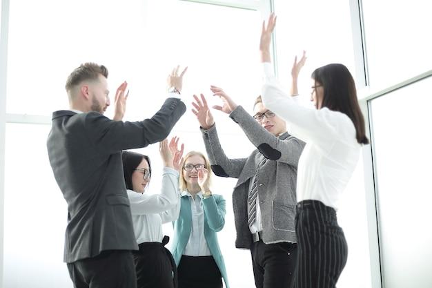 Business team verheugt zich, staande in het kantoor