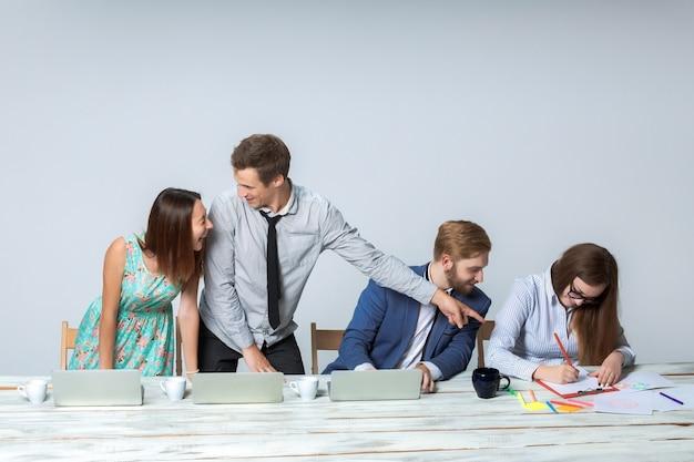 Business team werkt samen aan hun zakelijk project op kantoor op lichtgrijze achtergrond. allemaal glimlachend en kijkend naar de baas. de baas schrijft in een notitieboekje. copyspace afbeelding.