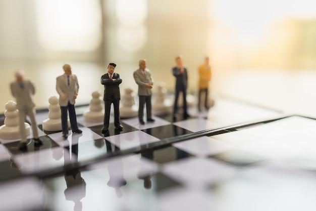 Business, teamwork en planning concept. sluit omhoog van cijfer van zakenman het miniatuurmensen status op schaakbord met pandschaakstukken en exemplaarruimte.