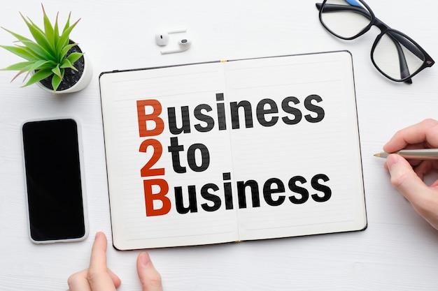 Business to business op een notitieboekje met persoon maakt aantekeningen.
