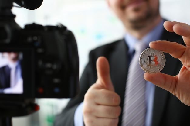 Business trainer houdt zilveren bitcoin in de hand